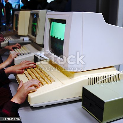 Children playing very old DOS games on vintage PS's. The monitor with visible screen is edited.