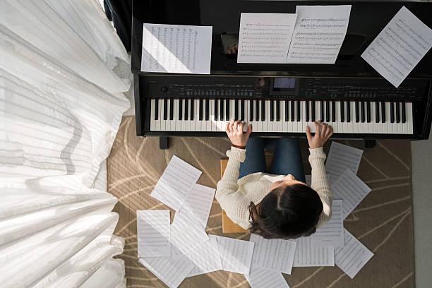 spielt klavier - piano noten stock-fotos und bilder