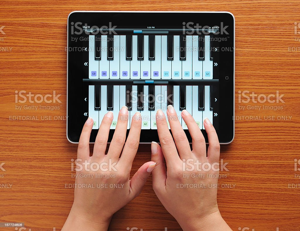 Playing piano with iPad stock photo