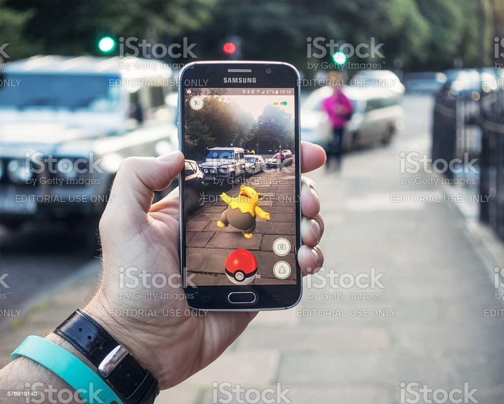 Playing Pokemon Go on the street Edinburgh, UK - July 18, 2016: Closeup of a man holding a Samsung S6 smartphone, playing Pokemon Go with the game's augmented reality superimposing a character onto the pavement surface, as a person approaches in the distance. 2016 Stock Photo
