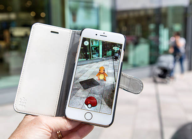 playing pokemon go on the street - mobile game stock photos and pictures