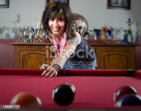 woman playing pool, and smiling at the camera.