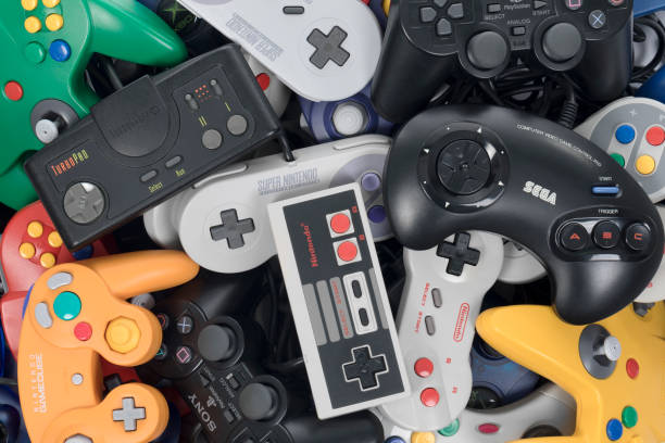 Playing Retro Video Games Taipei, Taiwan - February 19, 2018: A pile of retro video game controllers shot from above. nintendo stock pictures, royalty-free photos & images