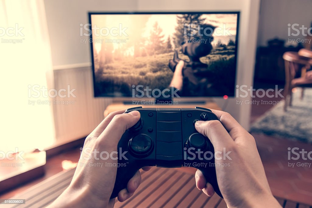 Playing shooter game on console stock photo
