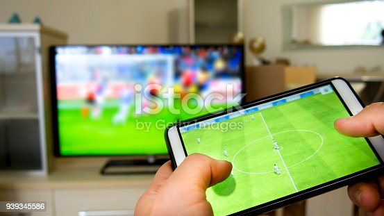 istock Playing soccer on a TV with a smartphone 939345586