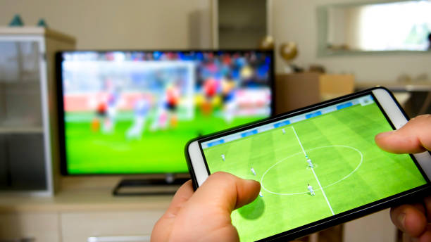 Playing soccer on a TV with a smartphone stock photo