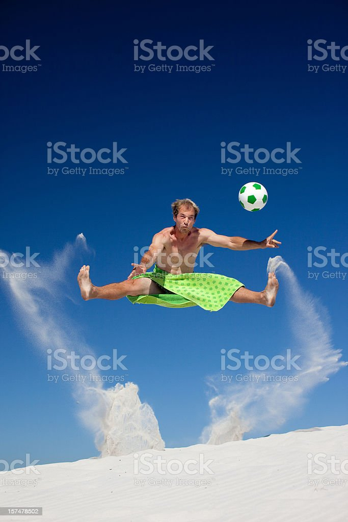 Playing soccer on the beach royalty-free stock photo
