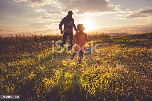 Grandfather and grandson playing soccer and football on the field in the nature