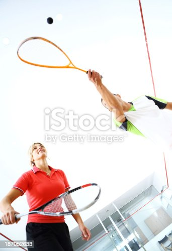 Low angle view of two adults playing squash indoors.the man is hitting the ball while she's prepared to return it. She's wearing red sports t-shirt and he's in white sports outfit.