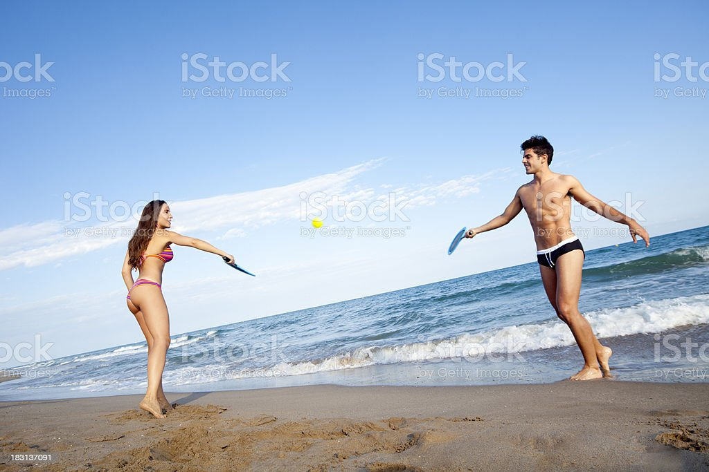 Playing tennis on the beach stock photo