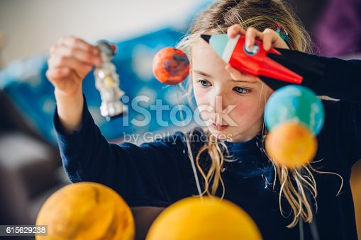 Little girl playing with her homemade planetarium as she holds an astronaut and spacecraft. Arms raised as she flies them over the planets.