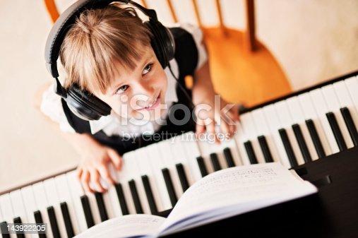 Beautiful ittle girl playing the digital piano.
