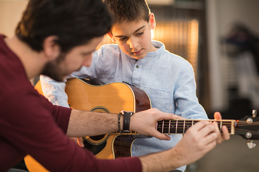 Young man teaching a boy to play the guitar
