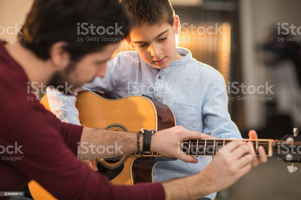 Playing the guitar with my brother stock photo