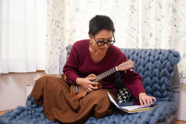 Playing the ukulele at home stock photo