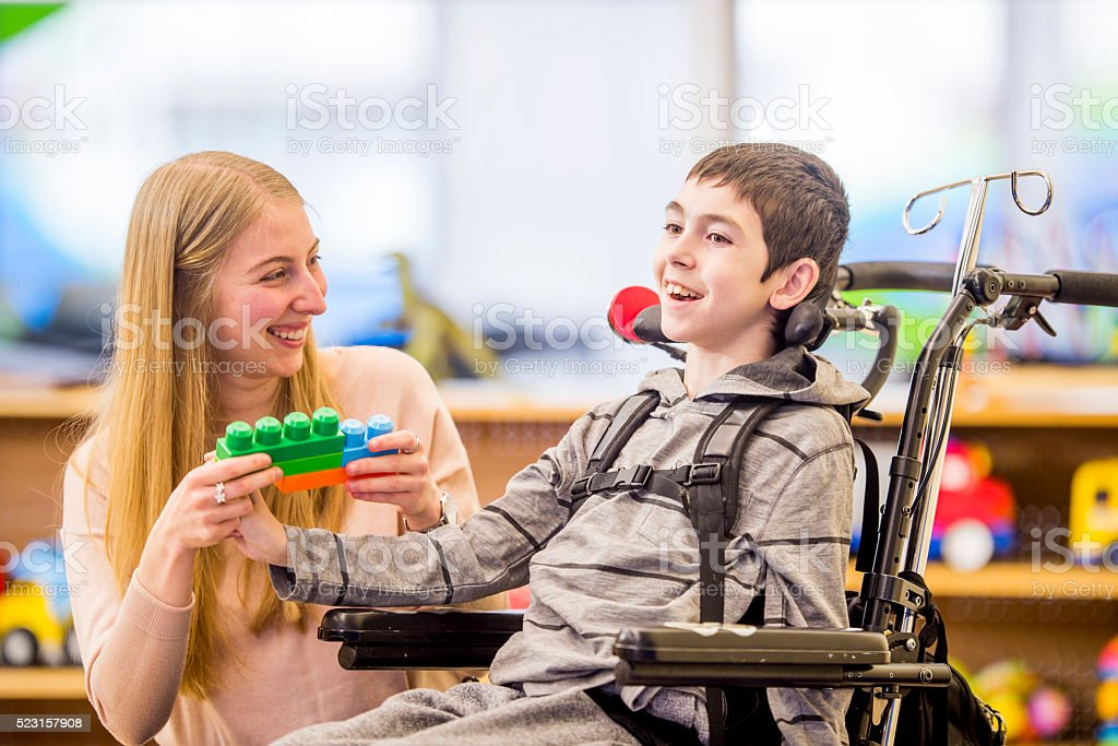 Playing Together with Toys A caregiver is helping a young boy with a physical disability play with plastic block toys. Adult Stock Photo