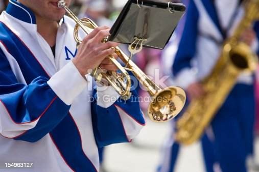 A trumpet player plays while marching in a parade