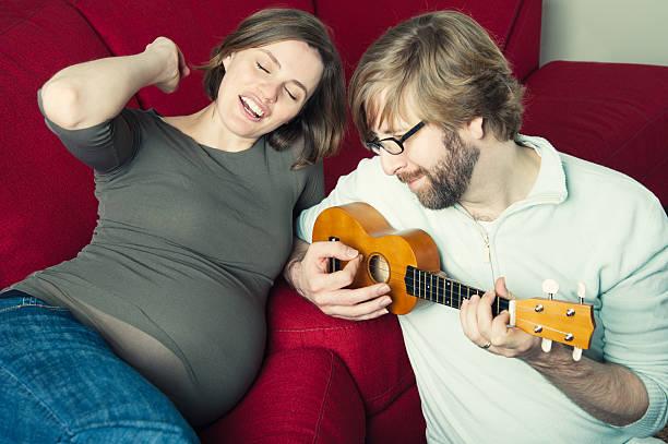 spielen wie man ukulele spielt und singt für das ungeborene kind. - ukulele songs stock-fotos und bilder