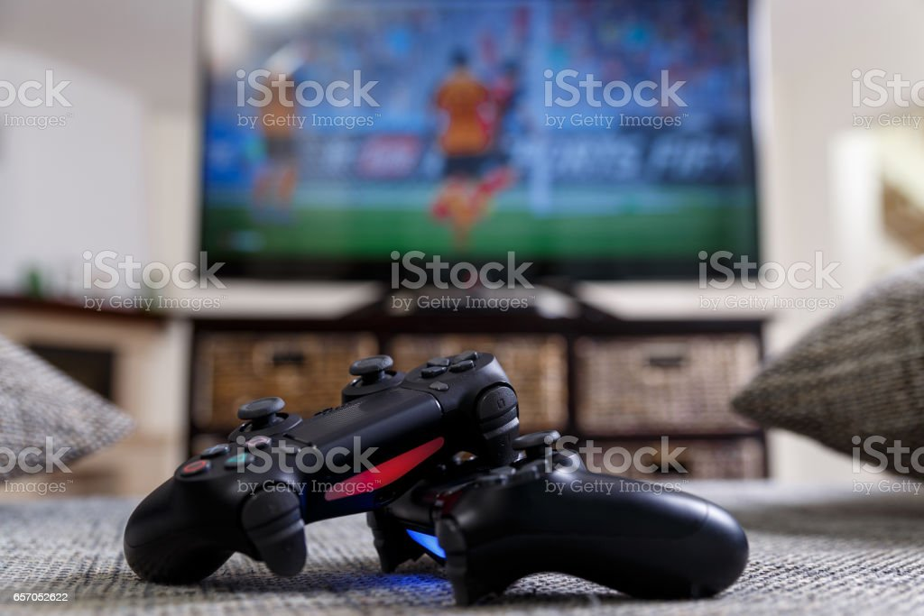 Playing video game. Console controllers. Playing video game. Console controllers or joysticks. Football or soccer game on the television. Widescreen tv stands on commode. Addict Stock Photo