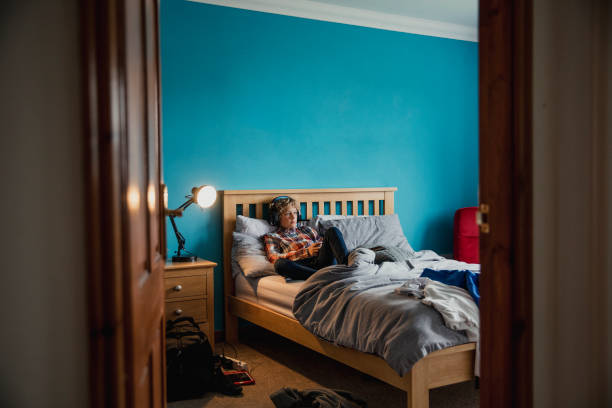 spielen videospiele - männliches schlafzimmer stock-fotos und bilder