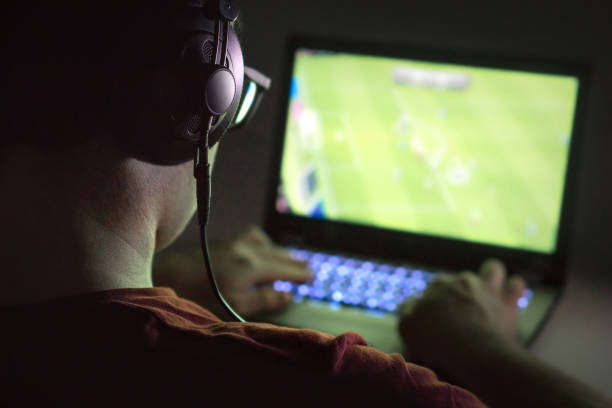 playing video games with laptop. young man plays online soccer or football on computer. back view of gamer with headphones in dark or late at night. - esports stock photos and pictures