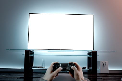 istock Playing videogame with joystick near blank white tv screen mockup 1129150108