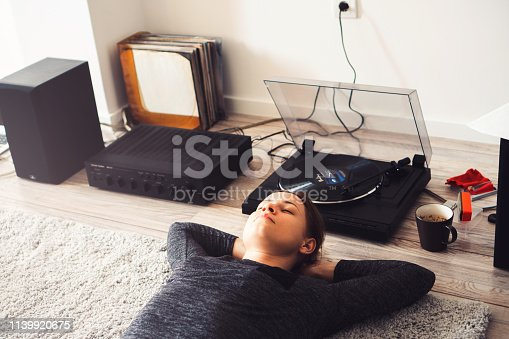 Young woman enjoy listening the music played on record player.