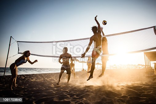Large group of friends playing volleyball on the beach.