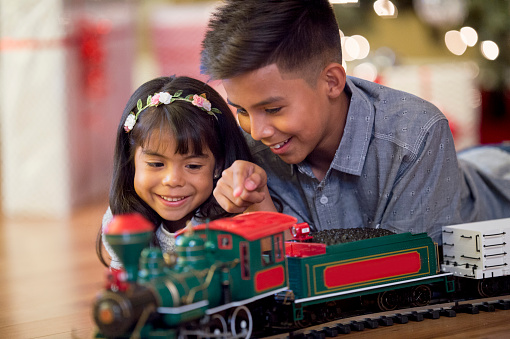A brother and sister are lying next to the Christmas tree and are plying with their new toy train.