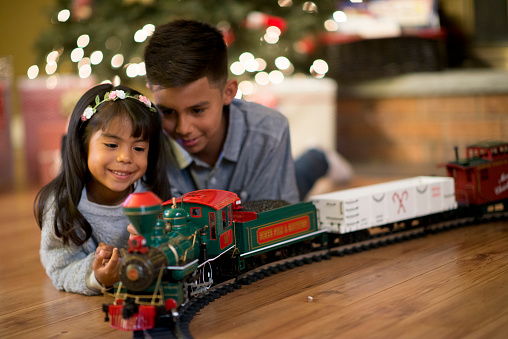 A brother and sister are playing with a toy train on Christmas morning. They are watching the train go around the tracks.