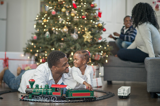 A family is spending time together at Christmas morning in their living room. A little girl is playing with a toy Christmas train.