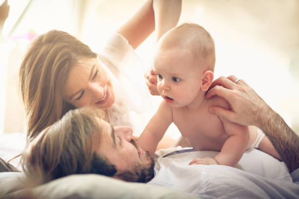 Playing with baby boy in bed. stock photo