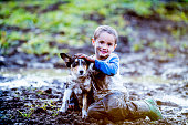 A boy is playing with his dog outside. They are sitting in a mud puddle. The boy looks happy but the dog does not.