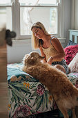A shot of a woman sitting down on her bed in her bedroom, she is playing with her pet dog.