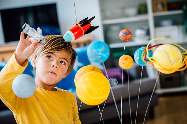 Playing with his Astronaut Little boy playing with his homemade planetarium as he holds an astronaut. A rocket hangs above. Arms raised as he plays. plant stem stock pictures, royalty-free photos & images