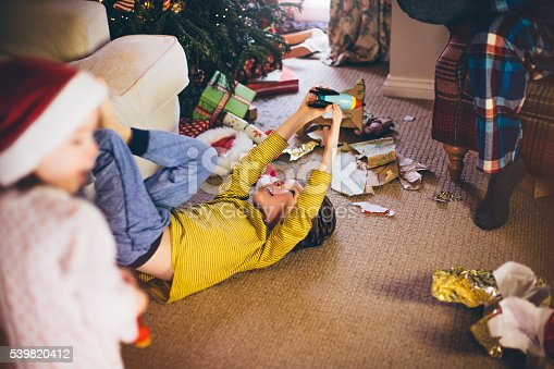 Little boy lying down on the living room floor in front of a Christmas tree playing with his new rocket ship toy.