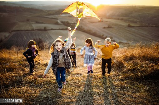 Large group of carefree kids running with a kite up the hill in autumn day. Focus is on girl with a kite looking at camera.
