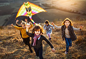 Large group of carefree kids running with a kite up the hill in autumn day. Focus is on boy with a kite looking at camera.