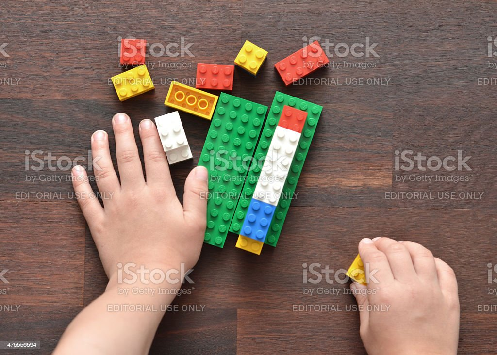Playing with Lego Vancouver, B.C., Canada -- May 28, 2015:Closeup of a 5 year old boy playing with Lego building blocks on a wood table.  Lego is a popular toy brand that is available worldwide.   2015 Stock Photo