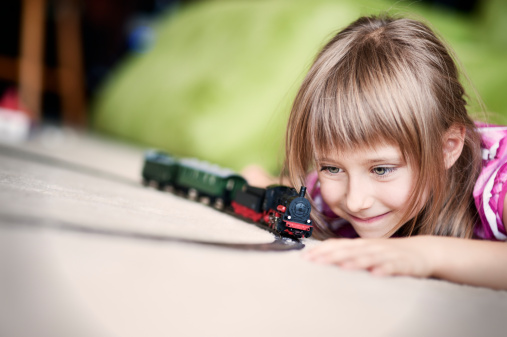 Smiling little girl lying on a carpet, playing with miniature train. Very shallow depth of field.