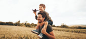 Young boy playing with an airplane while sitting on his father's shoulders
