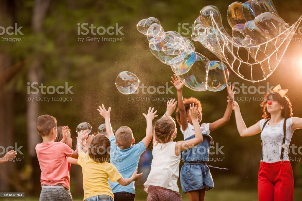 Playing with rainbow bubbles in the park! royalty-free stock photo