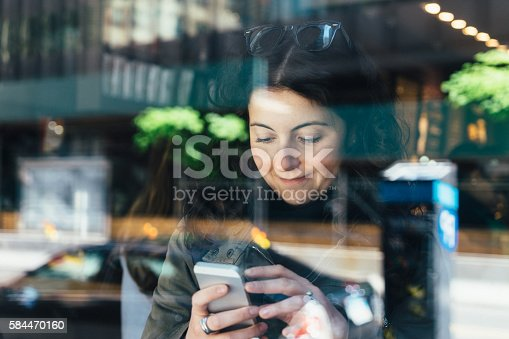 Young Adult Woman Playing With Smartphone At Café