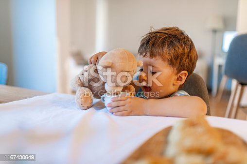 Adorable baby boy eating yogurt or milk. Little child feeding and playing with toy teddy bear. Playing with teddy bear at home. Childhood happiness concept.