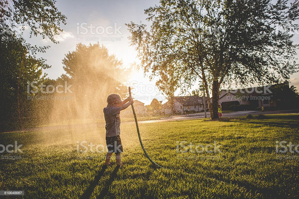Playing with the garden hose stock photo