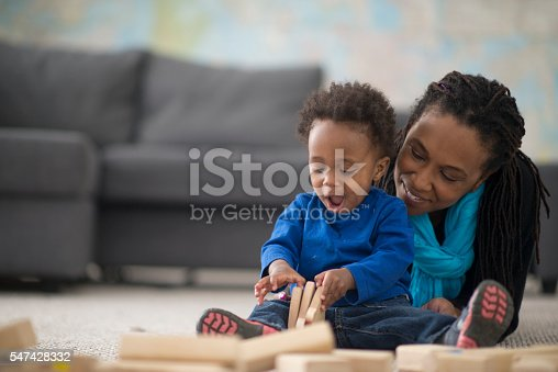 A mother is playing with her little boy in their home on mother's day. The toddler is playing with wooden building blocks.