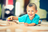"""""""Smiling little boy lying on a carpet, playing with little wooden train. Very shallow depth of field."""""""