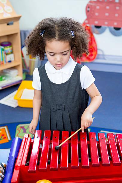 playing xylophone at nursery - lautbildungsspiele stock-fotos und bilder