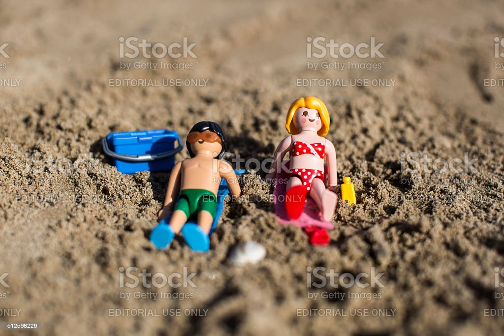 Playmobil man and woman figurine sun tanning on the sand. stock photo