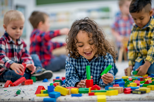 A group of preschool kids are playing indoors at a daycare center. One boy is lying on the floor and playing with colorful toy blocks.